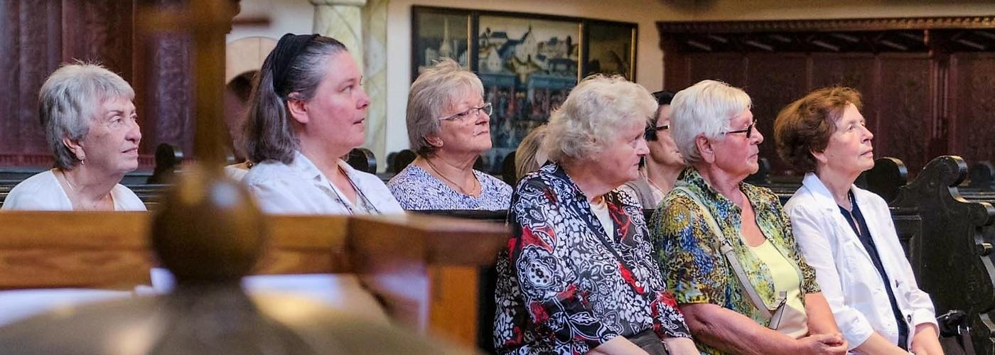 Zu sehen sind Teilnehmer des Frauenkreises auf einer Kirchenbank