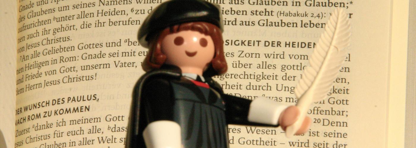 Das Bild zeigt Martin Luther als Playmobilfigur mit Feder und Bibel in der Hand, im Hintergrund der Römerbrief.